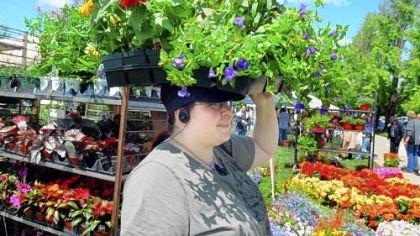 May Market Maggie Beatrous, 21, of North Hills carries some flowers with her head at Phipps Conservatory May Market on Friday, May 11, 2012.