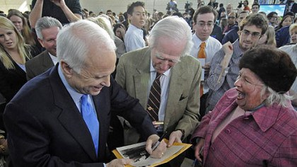 McCain signs photo Following his speech at Carnegie Mellon University, Sen. John McCain signs a photo for George J. Miller, of Fox Chapel, as Gwen Swaney laughs. The photo shows an naval vessel on which Mr. Miller served during World War II.