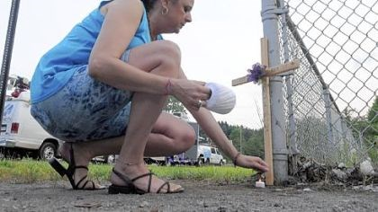 Memorial Tina Smith, of Monaca, places a cross outside the Horsehead Corp. plant on Thursday evening.