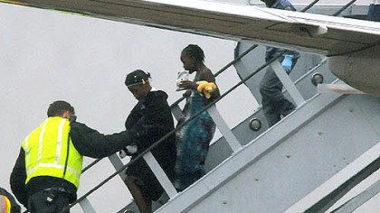 More children Getting a helping hand off the plane.