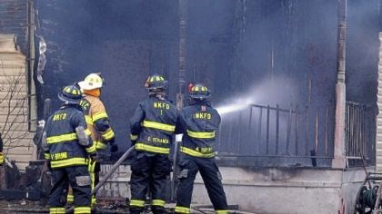 New Kensington fire Firefighters pour water on the burned-out entrance to the home along Seventh Street in New Kensington, where one person died and five others were injured on Wednesday.