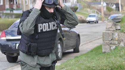 Officer dons gear An officer dons his gear as police respond after a man involved in a domestic dispute opened fire on police today Stanton Heights, killing three officers and injuring two others.