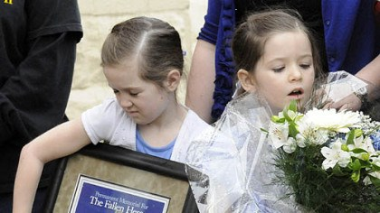 Officer's daughters The daughters of slain officer Stephen Mayhle -- Jennifer, 8, left, and Brooklynn, 5, clutch a plaque and flowers presented to the families of Mayhle, Eric Kelly and Paul Sciullo II following the dedication of a sculpture of St. Michael.