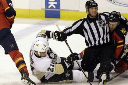 Penguins Craig Adams vs. Panthers Shawn Matthias The Penguins' Craig Adams and the Panthers' Shawn Matthias fight for the puck as referee Darren Gibbs gets caught between them during the
