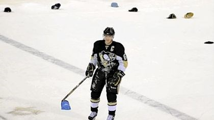 Pick-up duty Sidney Crosby helps pick up some of the hats tossed onto the ice after registering a hat trick Saturday night.