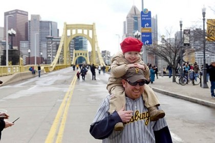PiratesOpeningDay_1 Jim Duzyk of Whitehall carries his daughter Keely, 3, on his shoulders while crossing the Roberto Clemente Bridge before the start of the Pittsburgh Pirates' home opener.