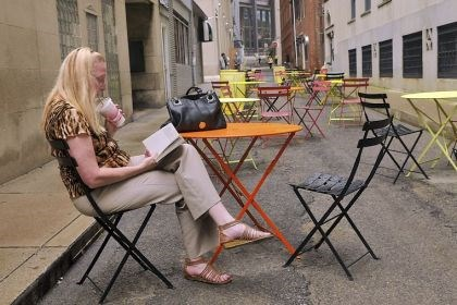pop-up patio Sharon McCracken of West Mifflin, who works Downtown, makes use of one of the tables Monday at the pop-up patio on Strawberry Way during her lunch break.