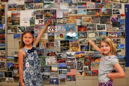 Postcards First-graders Emmerson Peffer, 7 and Paige Ditson, 7, of Connoquenessing Valley Elementary School, show some of the postcards the class collected this school year. Greetings arrived from all 50 states and a number of countries.