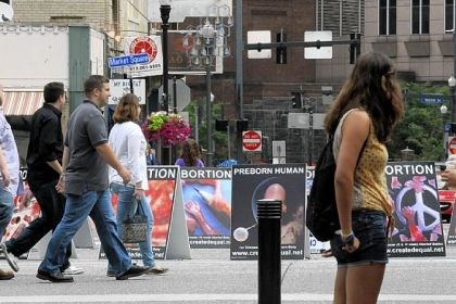 Posters Pedestrians walk by posters featuring images of aborted fetuses Friday in Market Square during lunchtime. The posters belonged to the anti-abortion group Created Equal.