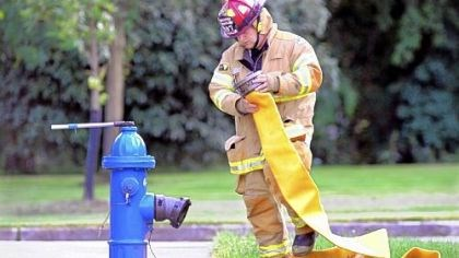 Practice Capt. Allen Morrow, volunteer firefighter from Moon, hooks up the hose to the hydrant during a pump practice drill.