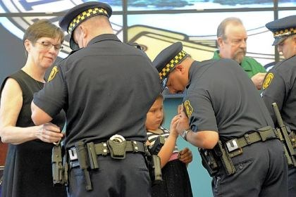 promotion ceremony From left, Noel Baker pins a new badge on her son, Sgt. Arthur Baker, while Grace DiGiacomo helps her father, Sgt. Robert DiGiacomo, and Albert Cecconello Jr. helps his son, Sgt. Albert Cecconello III, at their promotion ceremony at the Pittsburgh police bureau's North Side headquarters Friday.
