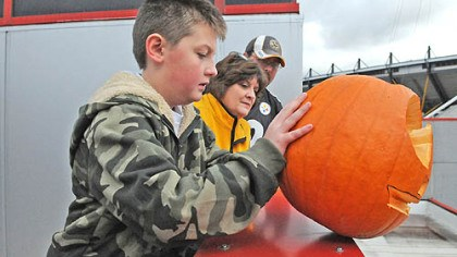Pumpkin drop Alexei Cramer, 10, of Latrobe pushes a pumpkin off the roof of the Carnegie Science Center as his grandmother, Cindy Cramer, and his father, Wes Cramer, watch. The activity helped teach children about the laws of physics.