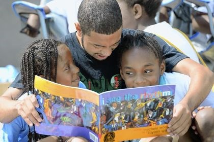 "readers Reading warrior Rondell Harris, 18, reads a book to Tianna Flewellen, left, 7, and Nyjorae Noel, 8, both of Lincoln-Lemington, on Tuesday during ""Public Display of Reading"" outside East Liberty Presbyterian Church."