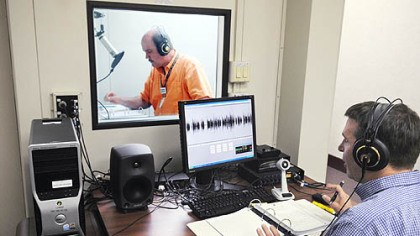 "Recording a book Don Ciccone reads from ""Spooky Pennsylvania"" in a sound booth while Mark Sachon monitors sound quality as it is digitally recorded. The text, stored in a digital cartridge, soon will be available to borrowers at the Carnegie Library for the Blind and Physically Handicapped."