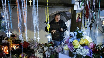 Remembering Ben Toby of Sandy Hook, Conn., visits a memorial to the Newtown shooting victims during a heavy rain early this morning.