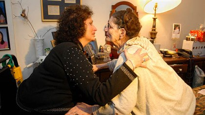 Reunited Jacquie Naughton, 59, greets her mother, Yolanda Massella, 83, in her bedroom in Mt. Lebanon after an absence of 31/2 years. Both women have muscular dystrophy, and Mrs. Massella is bedridden.
