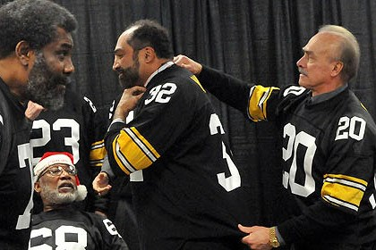 "Reunited steelers In a 2012 photo, Rocky Bleier, right, helps Franco Harris into his jersey before a group photo of Immaculate Reception alumni before a Steelers game. At left is Joe Greene and seated is ""Santa"" L.C. Greenwood."