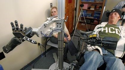 robotarm Assistant professor Jennifer Collinger, left, watches as quadriplegic research subject Tim Hemmes operates the mechanical prosthetic arm in a testing session at UPMC.