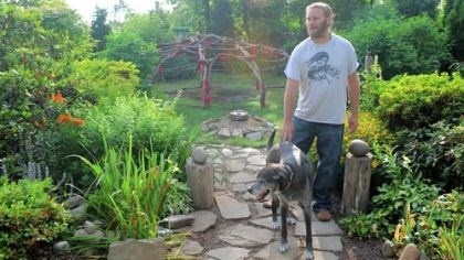 Sam and his dog Sam Lawther and his dog Draco on a path of pavers discarded by his landscaping clients. In the background is an Inipi sweat lodge == he made its frame from grapevines.
