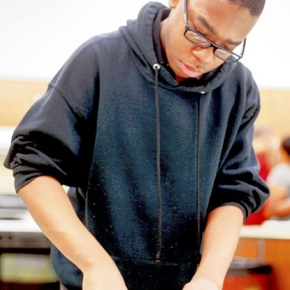 Sampson Obama Academy student Sampson practices knife skills while chopping lettuce.