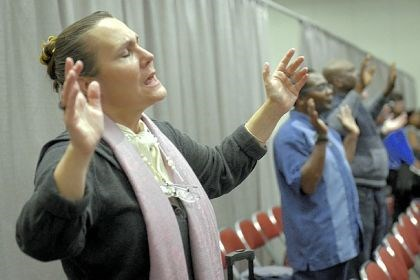 "Sandra Tyler worships Sandra Tyler, 54, originally from McKees Rocks, worships at a Benny Hinn Ministry event Wednesday night at the David L. Lawrence Convention Center, Downtown. Ms. Tyler is ""pastor to the homeless"" and homeless herself. She said she was skeptical of Mr. Hinn's monetary motivations, but thought he could still be used as a vehicle to worship God."