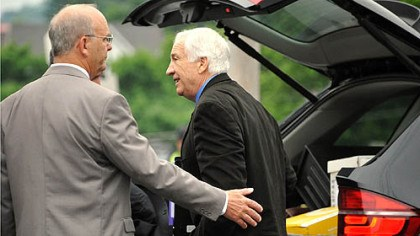 Sandusky Centre County Sheriff Denny Nau, left, helps Jerry Sandusky as he enters the Centre County Courthouse on Monday for the fifth day of testimony in his trial.
