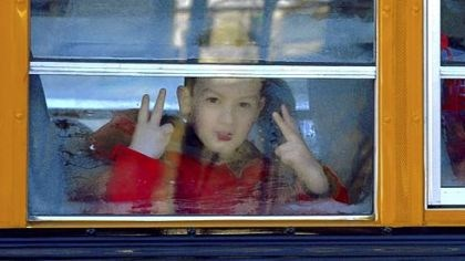 Sandy Hook A Sandy Hook Elementary student flashes peace signs as children leave on a school bus Thursday in Newtown, Conn.