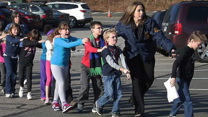 School evacuation Friday Connecticut State Police lead a line of children from the Sandy Hook Elementary School yesterday after the deadly massacre at the Newtown, Conn. school.