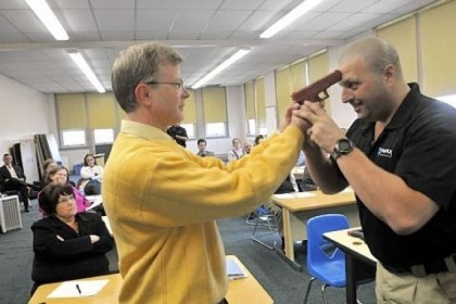 Sequence 2 In this three-photo sequence, Sam Rosenberg, black shirt, shows North Catholic High School religion teacher Greg Evans, left, how to disarm a gun-wielding intruder at close range during a session at the Troy Hill school on Monday.