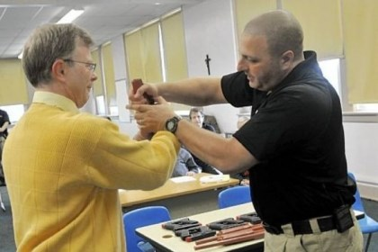 Sequence 3 In this three-photo sequence, Sam Rosenberg, black shirt, shows North Catholic High School religion teacher Greg Evans, left, how to disarm a gun-wielding intruder at close range during a session at the Troy Hill school on Monday.