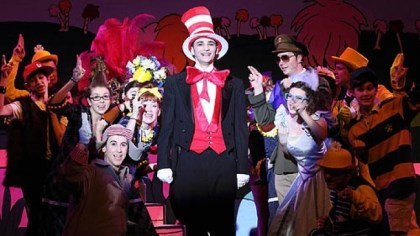 Seussical-3 The Cat in the Hat, played by Gabe DeRose-Elbaum. On the lower left is Horton the Elephant, played by Mark Klemencic and on the right is Gen. Schmitz, played by Phil Mashek and Gertrude McFuzz, played by Abby Rogers. They appear with some of the Gold Cast ensemble.