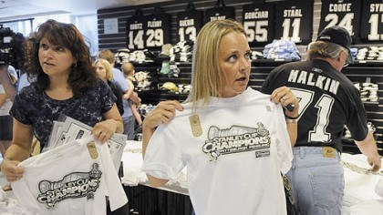 Shopping for Stanley Monica Hanley, right, of Knoxville, Tenn., sizes up a Stanley Cup champions shirt yesterday at PenStation at Mellon Arena.