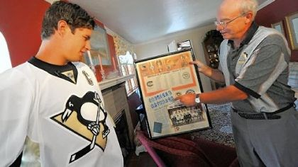 Sidney Crosby Sidney Crosby is shown the score sheet from 1967 by lifelong season-ticket holder David Disney after Crosby delivered Disney's season tickets yesterday. It marks the second season Penguins players helped deliver the tickets to their fan base.