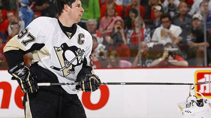 Sidney Crosby Penguins captain Sidney Crosby picks up his helmet after a scrum during Saturday's game at ScotiaBank Place in Ottawa.