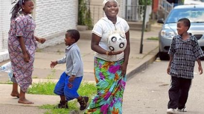 Somalian refugees Amina Muya plays kickball with family members on the street outside their Lawrenceville home.