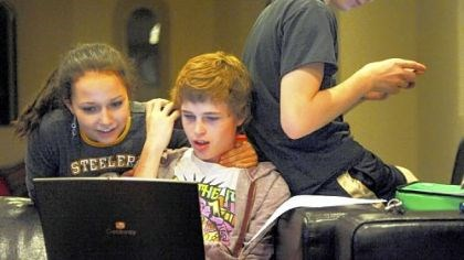 Student at the Byham House Elizabeth Truell, 15, looks over Cameron Clark's shoulder while he's on his computer as Seth Klein-Tooley, 13, of Spokane, Washington, checks his phone at the Pittsburgh Ballet Theatre's Byham house for out-of-town students.