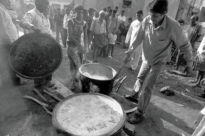 "Sunday dinner One of the images in ""Koraput Survivors Project,"" Sunday dinner following church service -- dal and rice, shows two Indian men carrying a pot of food that will serve the group."