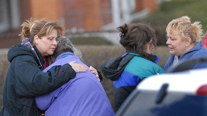 Suspect's family at scene Family members of the suspect in this morning's deadly standoff offer each other comfort at the scene.