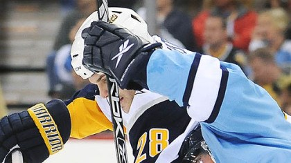 Tangled Sidney Crosby gets tangled with Buffalo's Paul Gaustad in the first period last night.