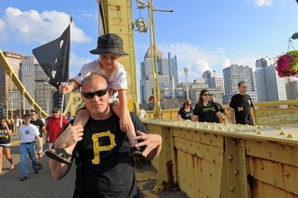 Terry Butt carries his son Jaden Terry Butt carries his son Jaden, 4, across the Clemente Bridge before the start of the Pirates game Friday night against the St. Louis Cardinals.