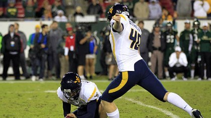 The attempt West Virginia's Michael Molinari, left, holds as kicker Tyler Bitancurt (40) winds up to attempt a game-winning field goal as time expires against South Florida last night in Tampa.