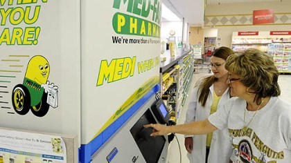 The machines Pharmacy technicians Rita Poljak and Crystal Olack demonstrate the Parata APM machine that remotely distributes filled prescriptions at the Med-Fast Pharmacy inside the Shop 'n Save in Bethel Park.