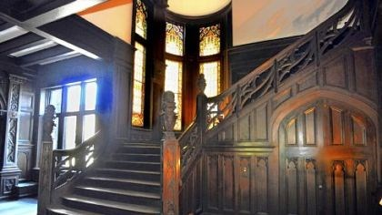 The McCook Mansion Light from stained glass windows casts a warm glow on the carved quartersawn oak wainscoting and staircase in the grand hall.