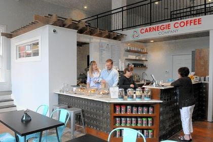 The perks From left, owner Ashley Comer, general manager Matt Harkness and employee Amanda Dille wait on customer Marlayne Derenzo of Crafton at the newly opened Carnegie Coffee Co. in Carnegie. The new shop is inside a long-vacant former post office.