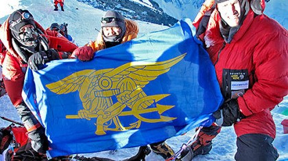 The summit Kenton Cool, Namgel and Michael Kobold raise the Navy SEAL flag on the summit of Mt. Everest.