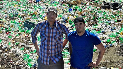 Thread LLC Ian Rosenberger, founder and CEO of Thread LLC, and Frank Macinsky, marketing director, stand in front of plastic waste in Haiti. Thread LLC is transporting 50,000 pounds of plastic flakes from Port au Prince's streets to the United States, where it eventually will be extruded into fiber.