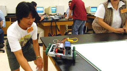 To catch a wayward robot Clarence Chu, of Dayton, Ohio, prepares to catch his team's wayward robot as his teammate Julie Sweeney, of Sioux City Iowa, watches during last week's robotics conference at Butler County Community College.