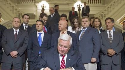 Tom Corbett Pennsylvania Gov. Tom Corbett signs the state budget late Saturday in Harrisburg.