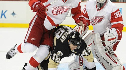 Tyler Kennedy, Brad Stuart and Chris Osgood Penguins forward Tyler Kennedy is knocked to the ice by Red Wings defenseman Brad Stuart in front of goaltender Chris Osgood.