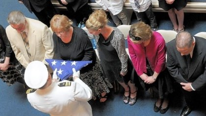 Veterans-2 Lt. Cmdr. Jeffrey Hawn presents to a family an American flag that had draped the coffin of a veteran.